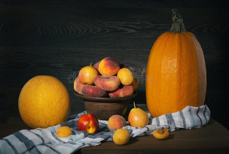 Ακόμα ζωή με τα ροδάκινα, την κολοκύθα, τα φρούτα και τα πεπόνια σε έναν ξύλινο πίνακα στοκ εικόνες