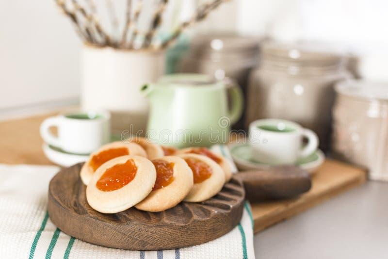 Ακόμα ζωή με τα σπιτικά μπισκότα με τη μαρμελάδα και το φρέσκο καφέ στον πίνακα πλησίον με τα λουλούδια Πρόγευμα στο εσωτερικό στοκ εικόνες με δικαίωμα ελεύθερης χρήσης