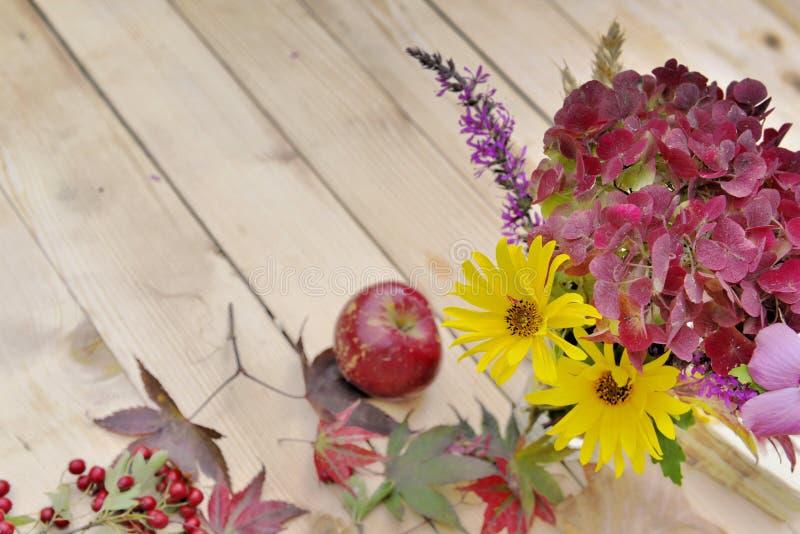 Ακόμα ζωή με τα όμορφα χρώματα των φθινοπωρινών λουλουδιών σε ένα ξύλινο υπόβαθρο στοκ φωτογραφία