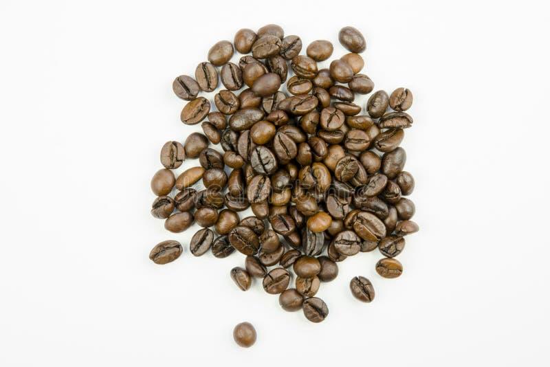 Ακόμα ζωή με την άποψη κινηματογραφήσεων σε πρώτο πλάνο των σιταριών του ψημένου καφετιού καφέ που απομονώνεται στοκ φωτογραφία