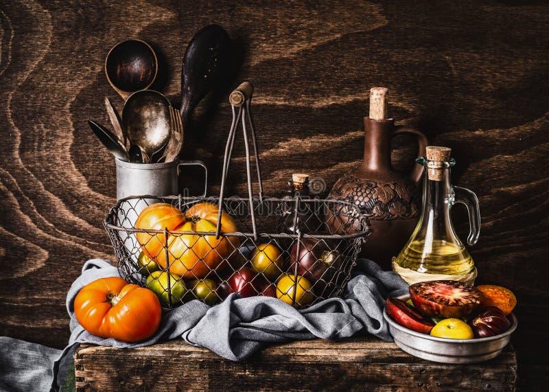 Ακόμα ζωή με τις ζωηρόχρωμες οργανικές ντομάτες στη συγκομιδή του καλαθιού, εργαλεία κουζινών, μπουκάλι ελαιολάδου σκοτεινό σε ξύ στοκ εικόνα