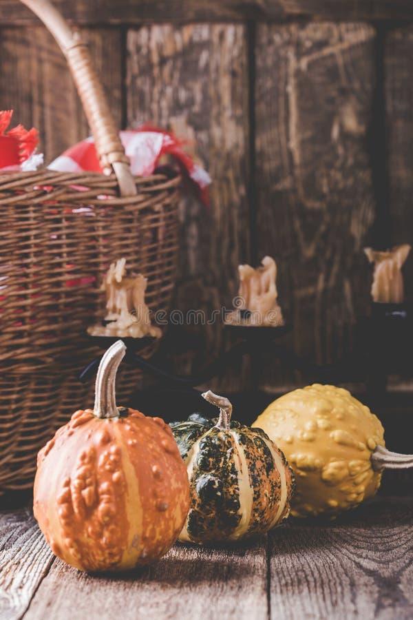 Ακόμα ζωή με τις κολοκύθες, κεριά, ψάθινο καλάθι και κόκκινος-ελεγγμένος στοκ εικόνα με δικαίωμα ελεύθερης χρήσης