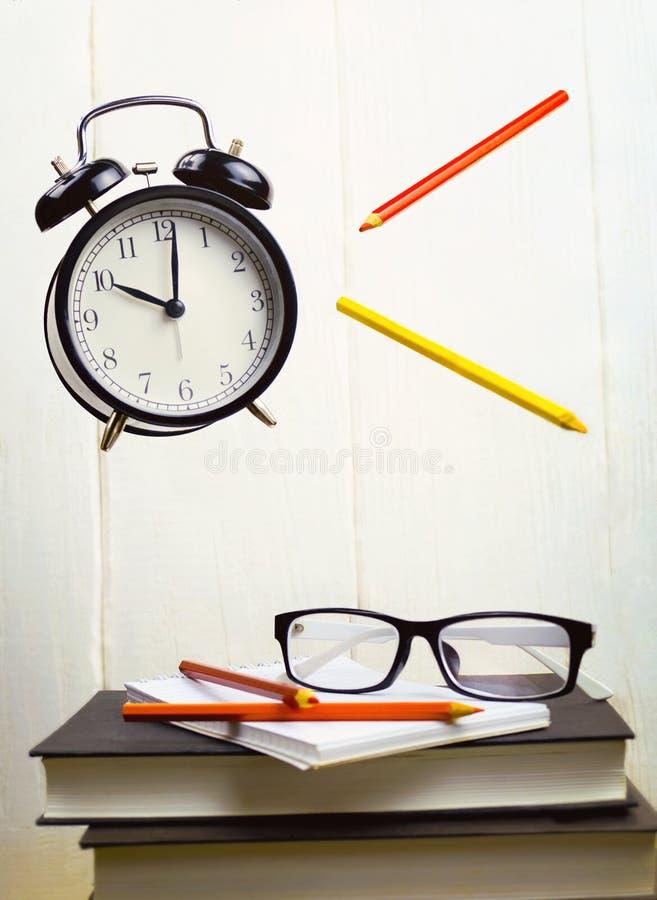 Ακόμα ζωή με το πετώντας ξυπνητήρι και τα χρωματισμένα μολύβια, βιβλία στοκ εικόνες