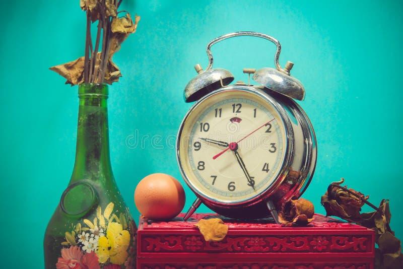 Ακόμα ζωή με το σπασμένο ξυπνητήρι, παλαιό βάζο γυαλιού με τα νεκρά ros στοκ φωτογραφίες