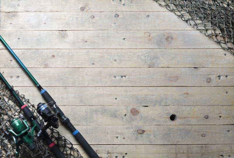Ακόμα-ζωή ράβδων διχτυών του ψαρέματος και αλιείας στο ξύλινο υπόβαθρο στοκ εικόνες
