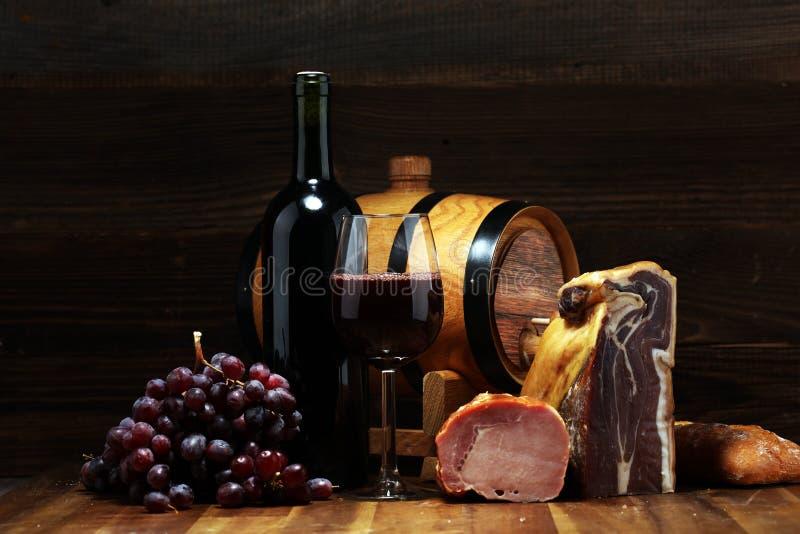 Ακόμα ζωή σε ένα αγροτικό ύφος Σταφύλια σε έναν ξύλινο πίνακα με ένα μπουκάλι του κρασιού και του κρέατος και του τυριού Antipast στοκ φωτογραφίες με δικαίωμα ελεύθερης χρήσης