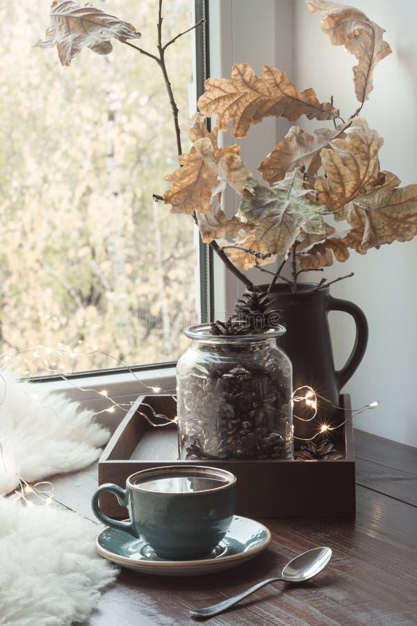 Ακόμα ζωή στο εγχώριο εσωτερικό Φλιτζάνι του καφέ στο σπίτι, γιρλάντα, σουηδική έννοια hygge στοκ φωτογραφίες