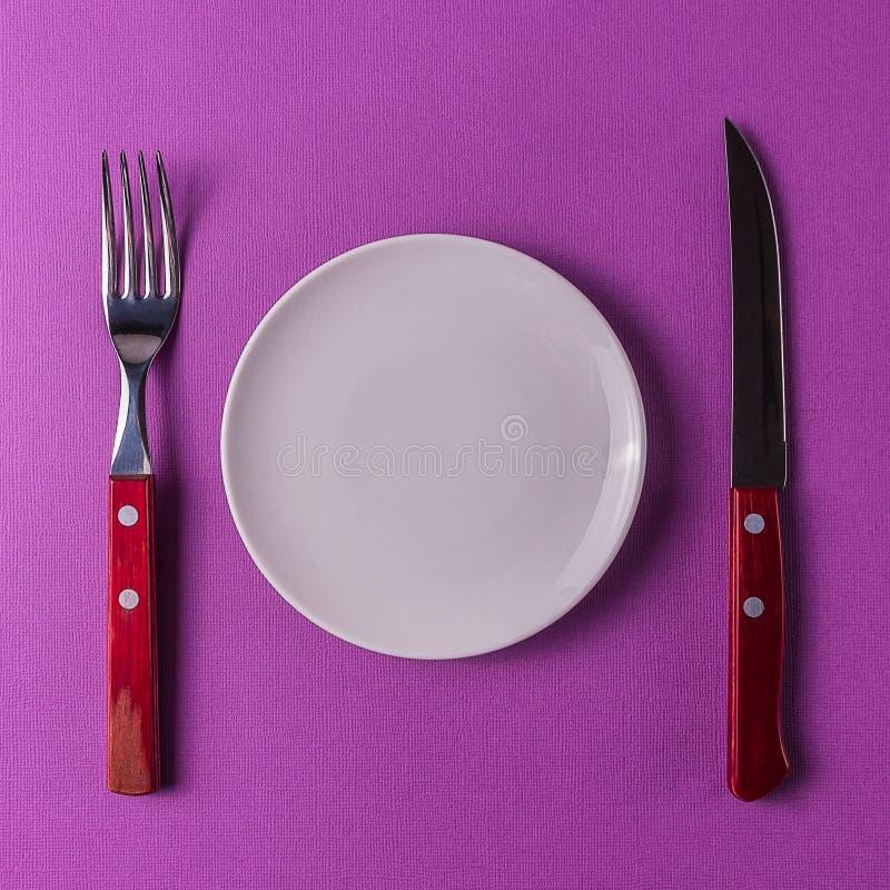 Ακόμα ζωή του άσπρου κενού πιάτου με τα μαχαιροπήρουνα στο χρωματισμένο backgrou στοκ εικόνες
