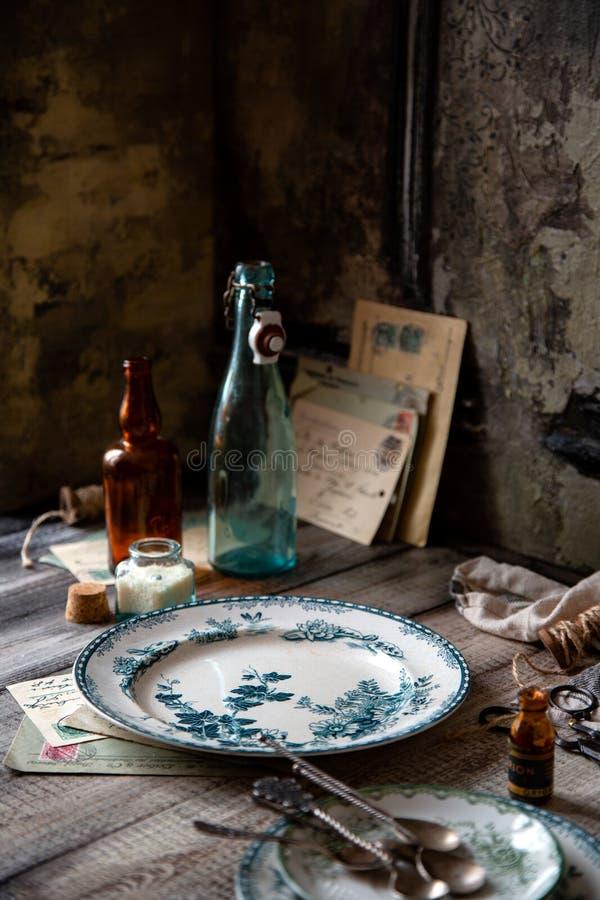 Ακόμα ζωή του εκλεκτής ποιότητας επιτραπέζιου σκεύους με τα κενά πιάτα με την πράσινη διακόσμηση, τα κουτάλια, τα παλαιές μπουκάλ στοκ εικόνες με δικαίωμα ελεύθερης χρήσης