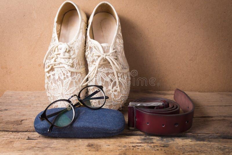 Ακόμα ζωή του παπουτσιού με τα γυαλιά και της ζώνης δέρματος στο ξύλο στοκ φωτογραφίες