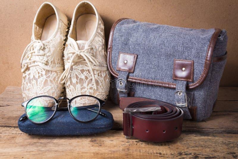 Ακόμα ζωή του παπουτσιού με τα γυαλιά, της ζώνης τσαντών και δέρματος στο ξύλο στοκ εικόνα