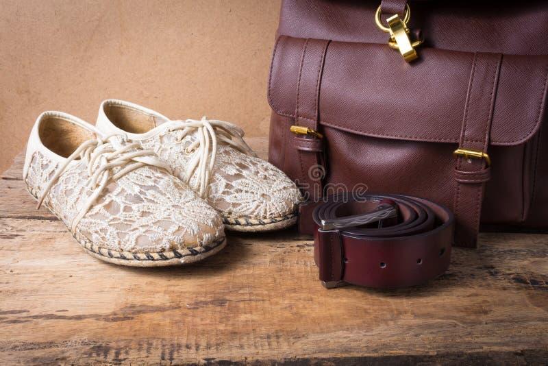 Ακόμα ζωή του παπουτσιού με την τσάντα δέρματος και της ζώνης δέρματος στο ξύλο στοκ φωτογραφία