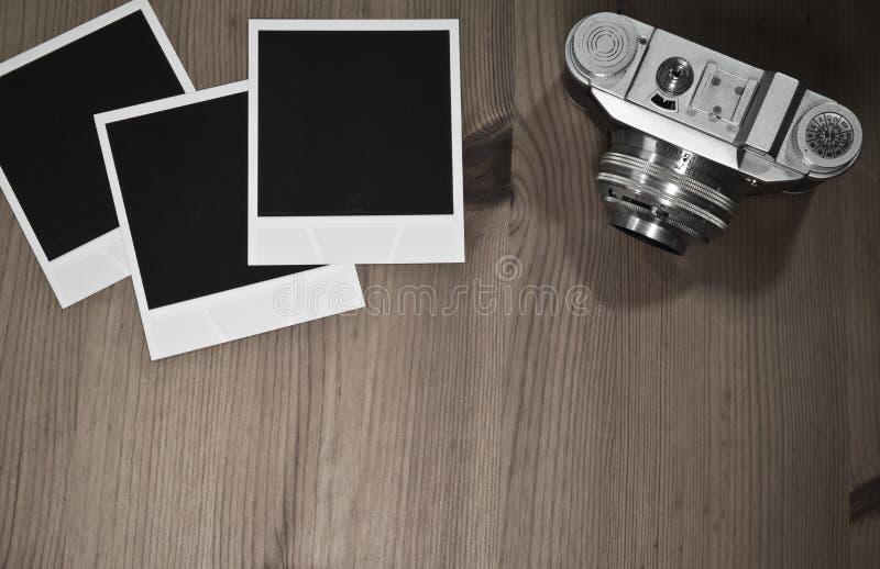 Ακόμα ζωή τρία κενά στιγμιαία πλαίσια φωτογραφιών στο παλαιό ξύλινο υπόβαθρο με την παλαιά αναδρομική εκλεκτής ποιότητας κάμερα μ στοκ εικόνες με δικαίωμα ελεύθερης χρήσης