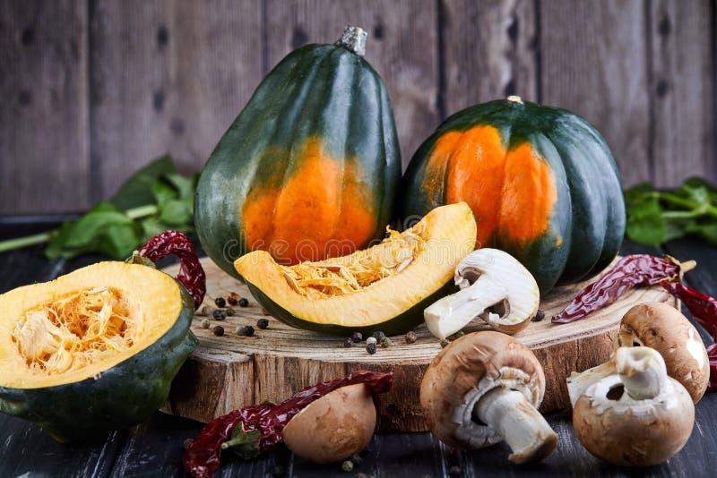 Ακόμα ζωή των πράσινος-πορτοκαλιών κολοκυθών κάστανων και της τεμαχισμένης κολοκύθας με το κόκκινο πιπέρι και των μανιταριών που  στοκ εικόνα με δικαίωμα ελεύθερης χρήσης