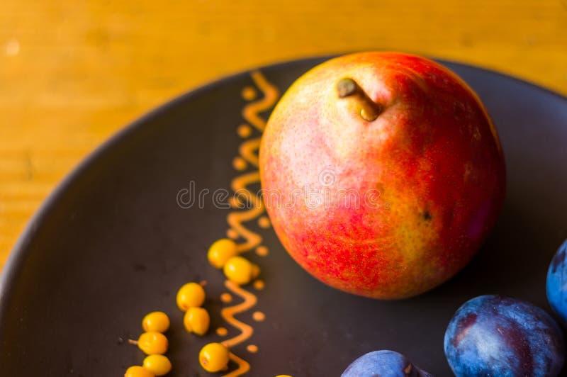 ακόμα ζωή - juicy μπλε δαμάσκηνα, μεγάλο ώριμο αχλάδι, και μούρα λευκαγκαθιών σε ένα κεραμικό πιάτο σε ένα ξύλινο υπόβαθρο στοκ φωτογραφία με δικαίωμα ελεύθερης χρήσης