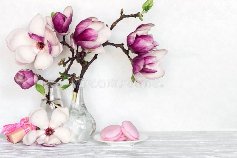 Ακόμα η ζωή με την ανθοδέσμη του ρόδινου magnolia ανθίζει στα μπουκάλια με το κιβώτιο δώρων και macaroons στον άσπρο πίνακα στοκ φωτογραφία με δικαίωμα ελεύθερης χρήσης