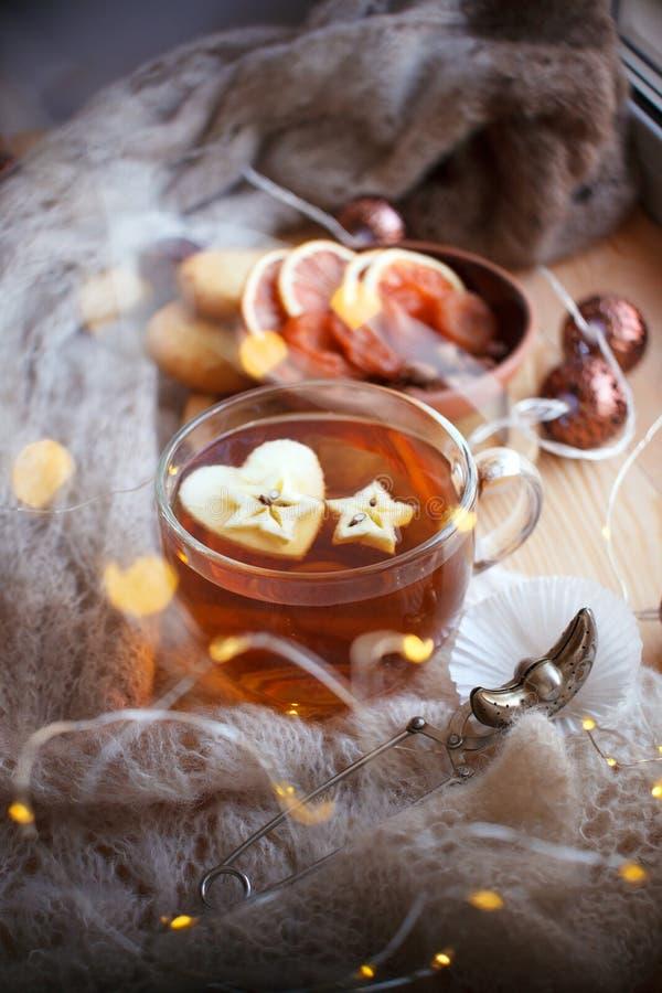 Ακόμα κατανάλωση τσαγιού ζωής στο καθιστικό Φλυτζάνι του τσαγιού με τον ελαφρύ ξύλινο πίνακα μήλων και γιρλαντών, η έννοια του co στοκ εικόνα