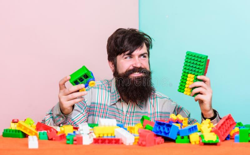 Ακόμα παιδί στην ψυχή του Πλαστικά τούβλα παιχνιδιού hipster ατόμων γενειοφόρα Δημιουργήστε τους φραγμούς κατασκευής Ζωηρόχρωμες  στοκ φωτογραφίες με δικαίωμα ελεύθερης χρήσης