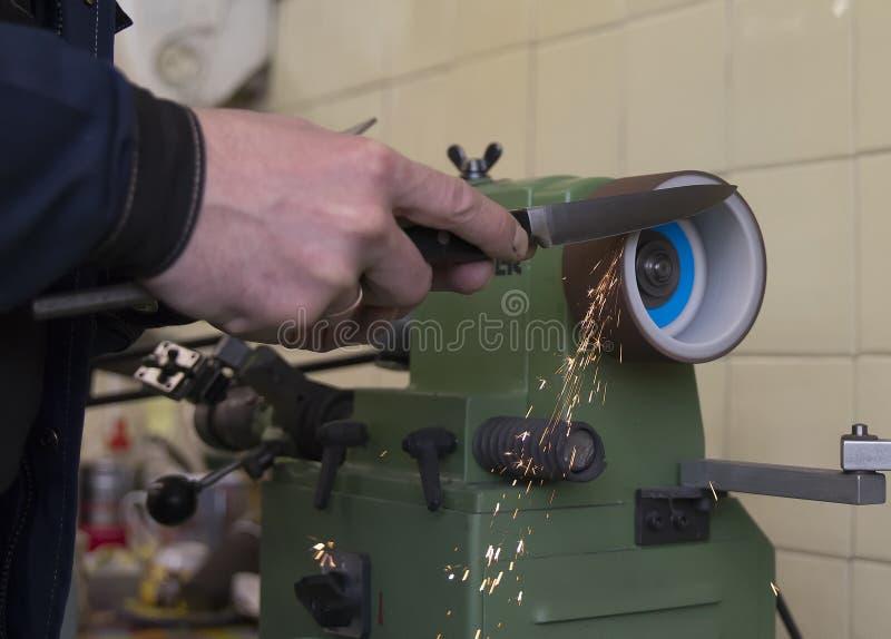 Ακόνισμα μαχαιριών στο εργαστήριο, χέρια εργαζομένων, σπινθηρίσματα στοκ εικόνες