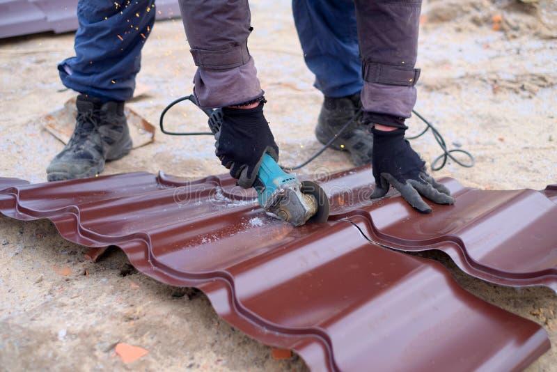 Αλέθοντας μηχανή χρήσης εργαζομένων για την κοπή του φύλλου υλικού κατασκευής σκεπής μετάλλων στοκ φωτογραφία με δικαίωμα ελεύθερης χρήσης