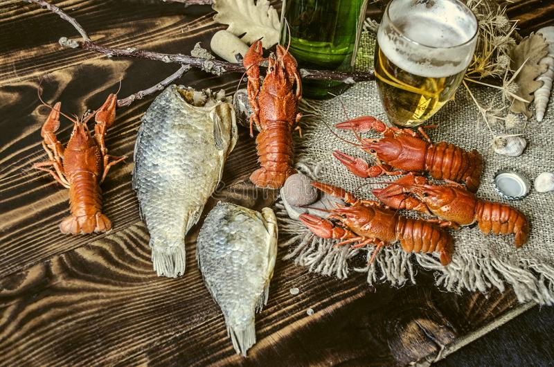 Αλατισμένοι βρασμένοι κόκκινοι αστακοί με τα αποξηραμένα παστά ψάρια, γυαλί με την μπύρα και ένα μπουκάλι της μπύρας στοκ φωτογραφία