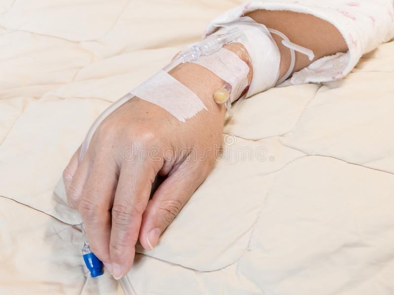 Αλατούχος ενδοφλέβια IV σταλαγματιά στη γυναίκα ` s παραδίδει το νοσοκομείο στοκ φωτογραφίες
