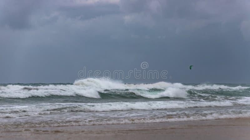 Αλεξίπτωτο Surfer σε έναν θυελλώδη ουρανό πέρα από τα foamy κύματα της Μεσογείου στοκ εικόνα