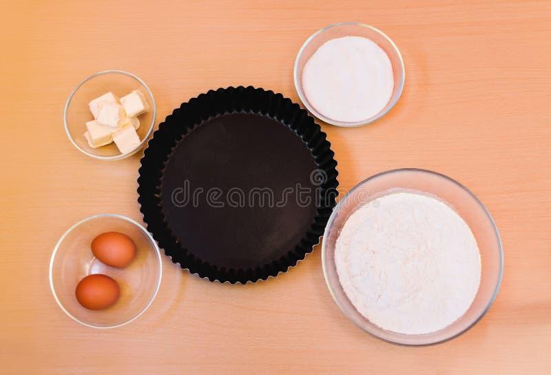 Αλεύρι, αυγά, ζάχαρη, βούτυρο και μορφή για το κέικ ψησίματος Τοπ όψη στοκ φωτογραφίες