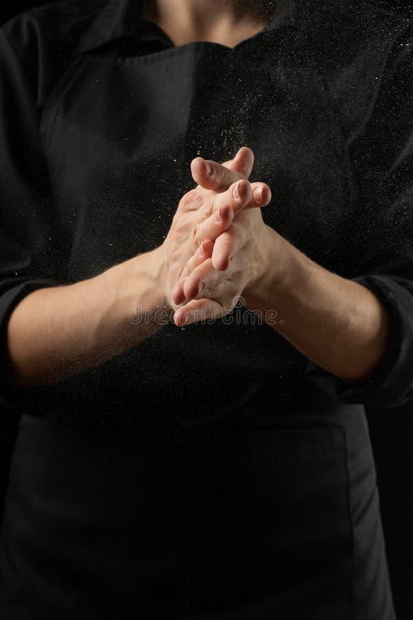 Αλεύρι βαμβακιού από το μάγειρα αρχιμαγείρων, παγωμένα μόρια στον αέρα Ψωμί, focaccia, πίτσα, ζυμαρικά έμβλημα σε ένα μαύρο υπόβα στοκ εικόνες