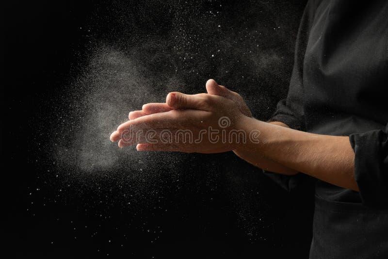 Αλεύρι βαμβακιού από το μάγειρα αρχιμαγείρων, παγωμένα μόρια στον αέρα Ψωμί, focaccia, πίτσα, ζυμαρικά έμβλημα σε ένα μαύρο υπόβα στοκ φωτογραφία με δικαίωμα ελεύθερης χρήσης