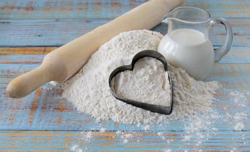Αλεύρι, κυλώντας καρφίτσα, καρδιά πιάτων ψησίματος και κανάτα γυαλιού με το γάλα μεταξύ του άσπρου αλευριού σίτου στον μπλε ξύλιν στοκ εικόνα