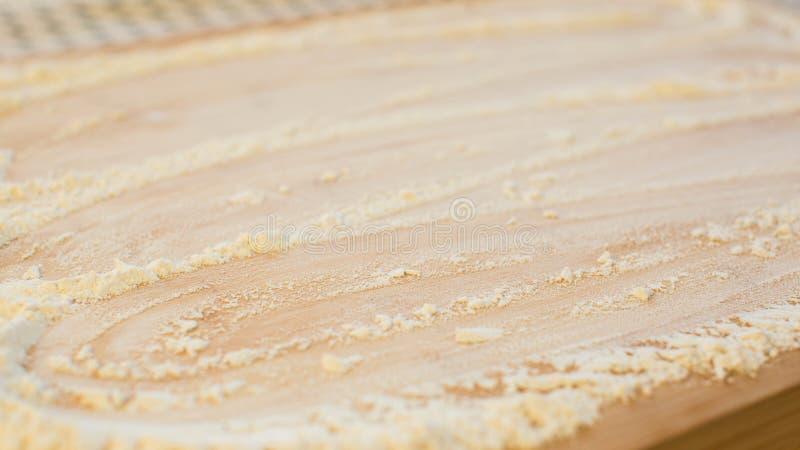 Αλεύρι σε έναν ξύλινο τέμνοντα πίνακα στοκ εικόνες