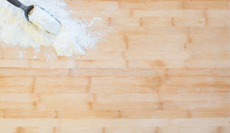 Αλεύρι σε έναν ξύλινο τέμνοντα πίνακα στοκ φωτογραφίες