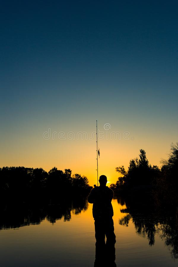 Αλιεία στη λίμνη στο ηλιοβασίλεμα Σκιαγραφία ενός ψαρά στοκ εικόνα με δικαίωμα ελεύθερης χρήσης