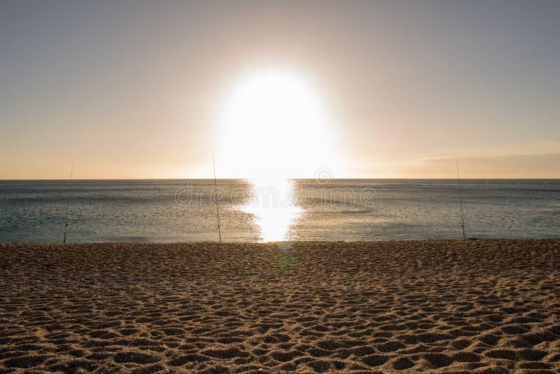 Αλιεία των ράβδων στην ανατολή σε μια παραλία στοκ φωτογραφία