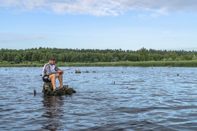 Αλιεία Ψαράς στη δράση, μόνα ψάρια σύλληψης ατόμων με την περιστροφή της ράβδου στοκ φωτογραφία