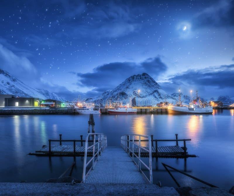 Αλιευτικά σκάφη κοντά στην αποβάθρα στη θάλασσα και τα χιονώδη βουνά τη νύχτα στοκ φωτογραφίες με δικαίωμα ελεύθερης χρήσης