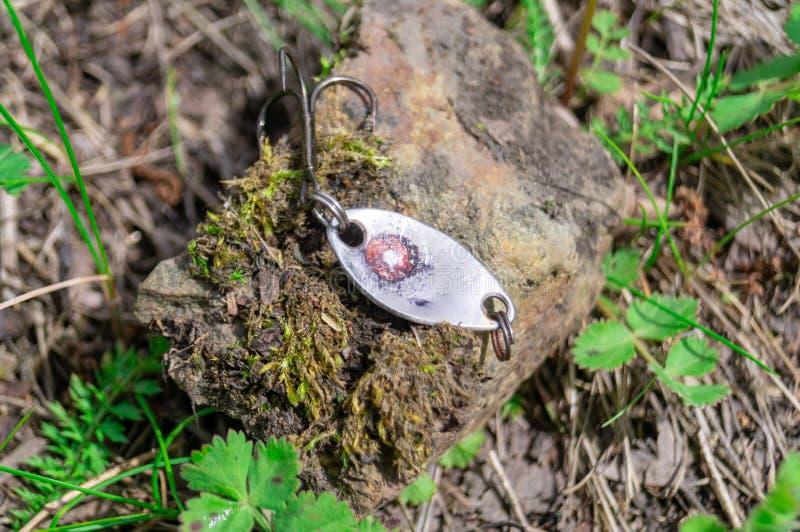 Αλιεύοντας εξαρτήματα Μπιχλιμπίδια και θέλγητρα που βρίσκονται σε μια πέτρα με ένα δασικό υπόβαθρο στοκ εικόνα