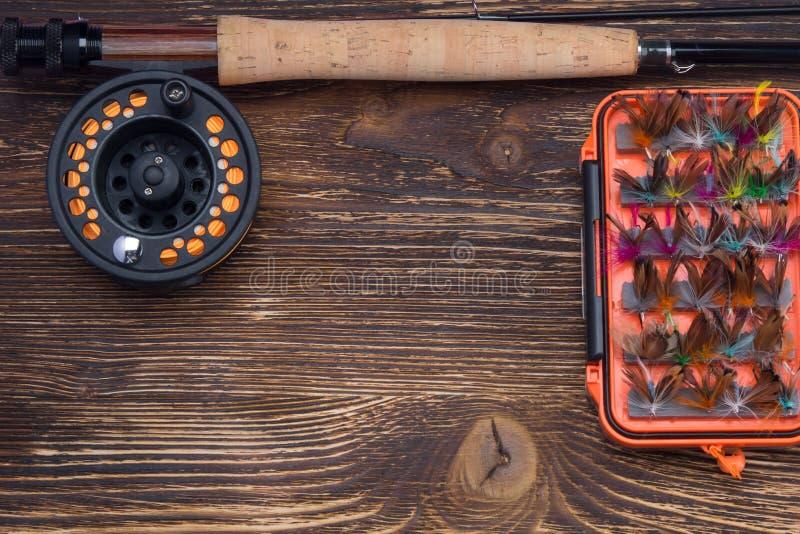 Αλιεύοντας τη ράβδο με ένα εξέλικτρο και ένα σύνολο δολώματος, κουνούπια, πεταλούδες και σκώροι, σε έναν σκοτεινό παλαιό πίνακα,  στοκ εικόνες