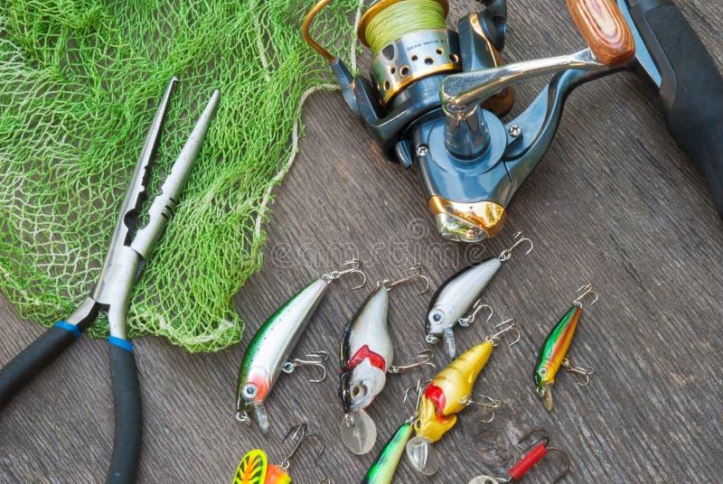 Αλιεύοντας τον εξοπλισμό - η περιστροφή, οι γάντζοι και τα θέλγητρα αλιείας σκουραίνουν επάνω το ξύλινο υπόβαθρο στοκ φωτογραφία