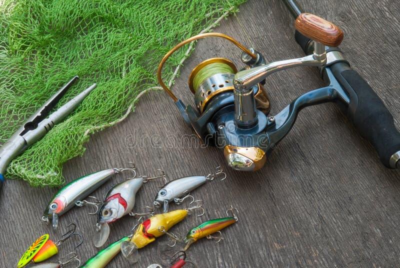 Αλιεύοντας τον εξοπλισμό - η περιστροφή, οι γάντζοι και τα θέλγητρα αλιείας σκουραίνουν επάνω το ξύλινο υπόβαθρο στοκ εικόνα με δικαίωμα ελεύθερης χρήσης