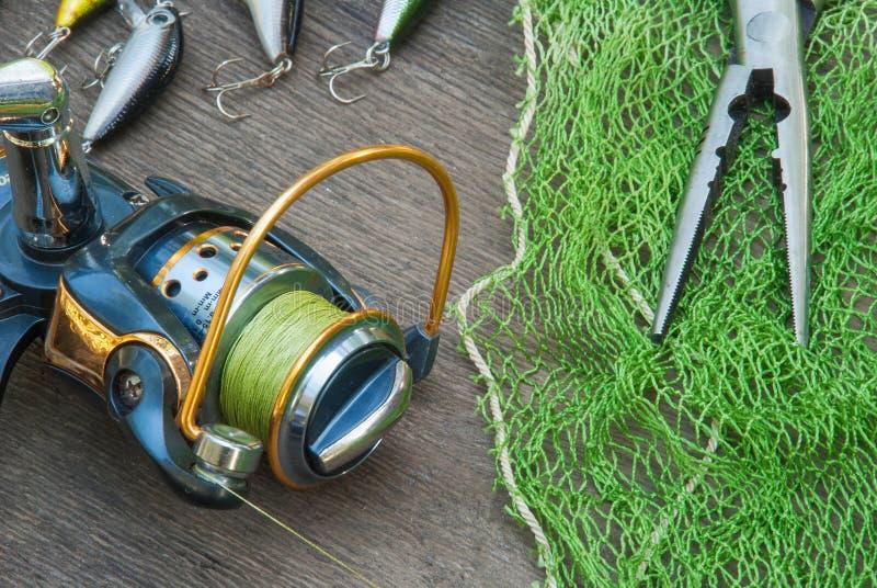 Αλιεύοντας τον εξοπλισμό - η περιστροφή, οι γάντζοι και τα θέλγητρα αλιείας σκουραίνουν επάνω το ξύλινο υπόβαθρο στοκ εικόνες με δικαίωμα ελεύθερης χρήσης