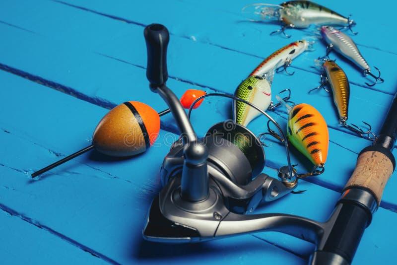 Αλιεύοντας τον εξοπλισμό - η περιστροφή, οι γάντζοι και τα θέλγητρα αλιείας σκουραίνουν επάνω το ξύλινο υπόβαθρο στοκ φωτογραφία με δικαίωμα ελεύθερης χρήσης