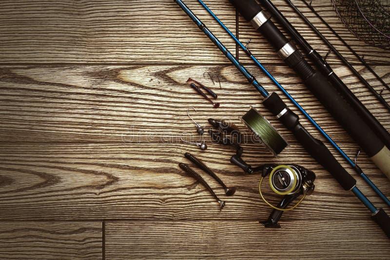 Αλιεύοντας τον εξοπλισμό - η περιστροφή, οι γάντζοι και τα θέλγητρα αλιείας σκουραίνουν επάνω το ξύλινο υπόβαθρο r στοκ εικόνες με δικαίωμα ελεύθερης χρήσης