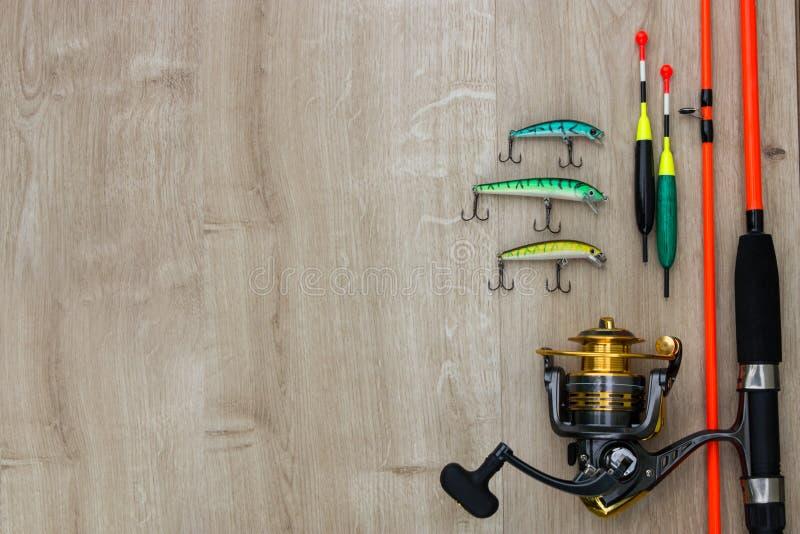 Αλιεύοντας τον εξοπλισμό - περιστροφή, γάντζοι και θέλγητρα αλιείας στο άσπρο ξύλινο υπόβαθρο r στοκ εικόνες
