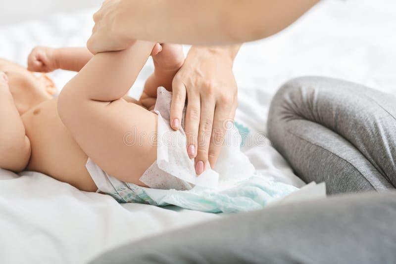 Αλλαγή πάνας Η μητέρα σκουπίζει τους γλουτούς του μωρού με υγρούς ιστούς στοκ εικόνα με δικαίωμα ελεύθερης χρήσης