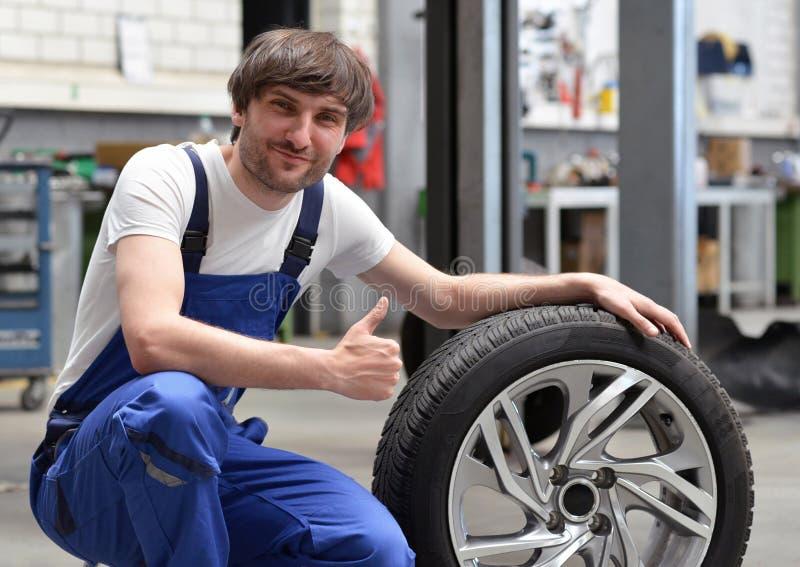 Αλλαγή ροδών σε ένα εργαστήριο αυτοκινήτων από το μηχανικό - πορτρέτο og που χαμογελά στοκ φωτογραφία με δικαίωμα ελεύθερης χρήσης