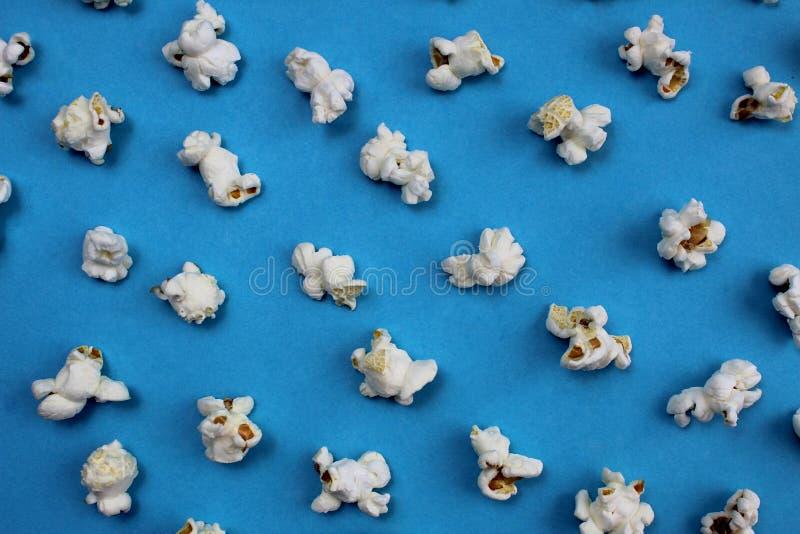 Αλμυρό τραγανό πρόσφατα μαγειρευμένο popcorn σύστασης σε ένα μπλε υπόβαθρο στοκ εικόνα με δικαίωμα ελεύθερης χρήσης