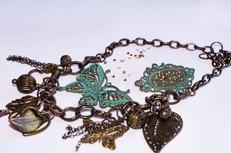 Αλυσίδα χαλκού με τις διακοσμητικές πεταλούδες, τα φύλλα, τα λουλούδια και τις χάντρες στοκ φωτογραφία