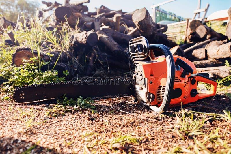 Αλυσιδοπρίονο μπροστά από έναν σωρό των ξύλινων κούτσουρων στοκ εικόνες